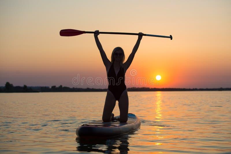 La natación atractiva joven de la mujer encendido se levanta el tablero de paleta Deportes acuáticos, forma de vida activa imagenes de archivo