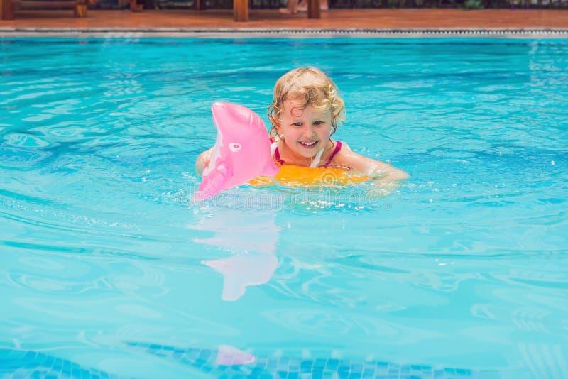 La natación bonita de la niña en piscina al aire libre y se divierte con foto de archivo libre de regalías