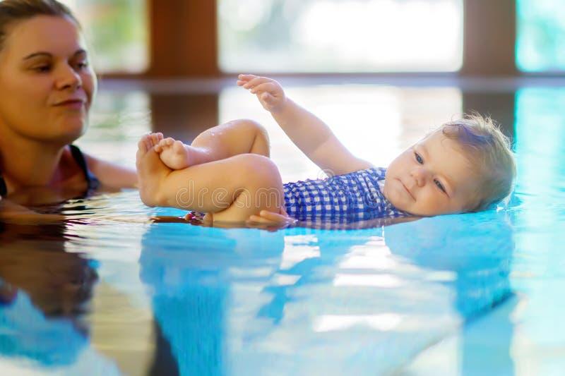 La natación feliz de la madre con la hija adorable linda del bebé en balneario del gasto de la piscina vacations fotografía de archivo libre de regalías