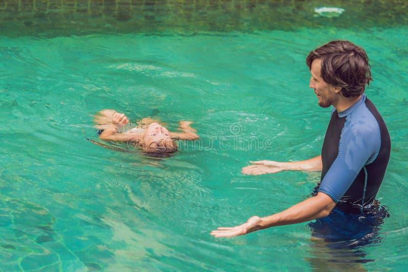 La natación masculina del instructor para los niños enseña a un muchacho feliz a nadar en la piscina imagen de archivo