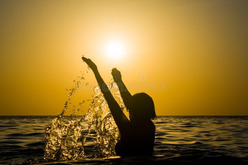 La nataci?n de la muchacha en el mar en la puesta del sol, salpica del agua de la transparencia, silueta negra femenina foto de archivo
