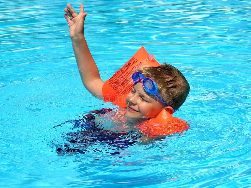 La natation heureuse de garçon dans la piscine extérieure dans le bras se hérisse photo libre de droits