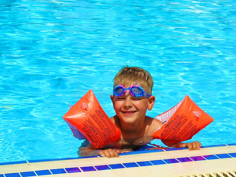 La natation heureuse de garçon dans la piscine extérieure dans le bras se hérisse image stock
