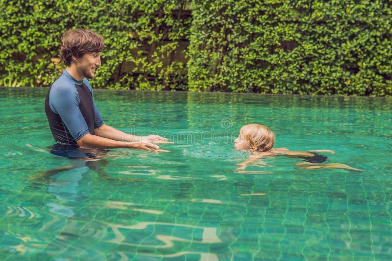 La natation masculine d'instructeur pour des enfants enseigne un garçon heureux à nager dans la piscine photos stock