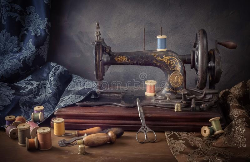 La natura morta con una macchina per cucire, forbici, infila fotografia stock libera da diritti
