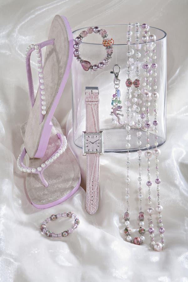 La natura morta delle catene rosa della collana guarda e Flip-flop su raso bianco fotografia stock libera da diritti