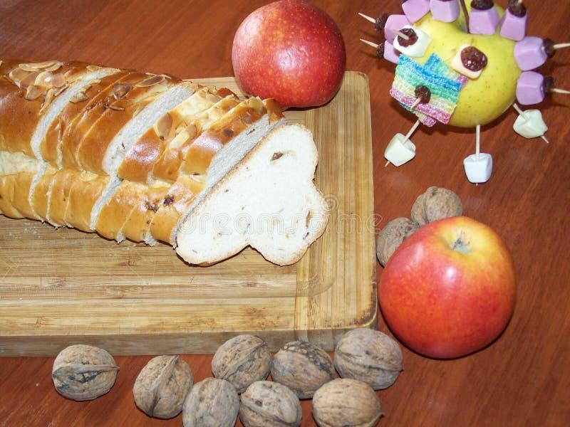 La natura morta di arrivo con il Natale tricotta il pane, le mele ed i dadi Apple ha decorato le caramelle Su una tavola del bord fotografia stock libera da diritti