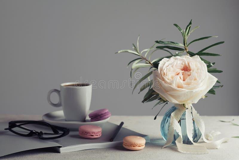 La natura morta di mattina con l'annata è aumentato in un vaso, in un caffè e nei macarons su una tavola leggera Bella e prima co immagini stock libere da diritti