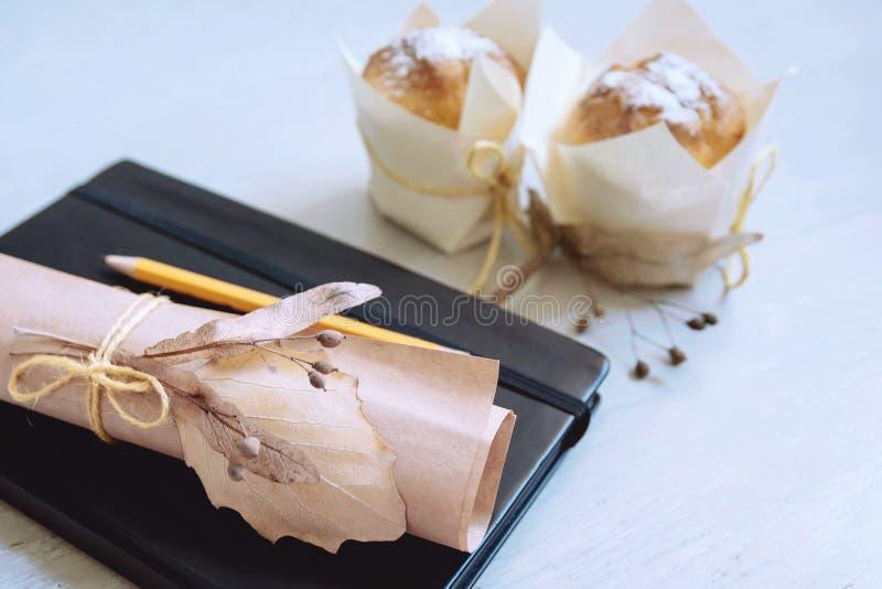 La natura morta ha piegato la carta in bianco, decorata con i fiori secchi Area di lavoro con il taccuino e la matita con lo spaz immagini stock