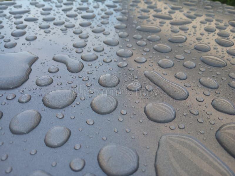 La nature de grandes gouttelettes d'eau sur le métal Boues d'eau sur fond métallique noir, eau et texture métallique photo stock