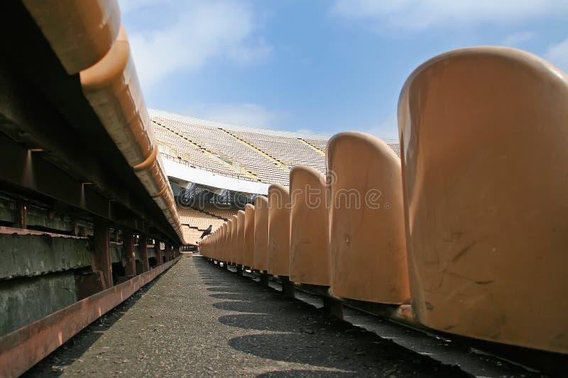 La navata laterale fra le file nella sala vuota dello stadio enorme immagine stock