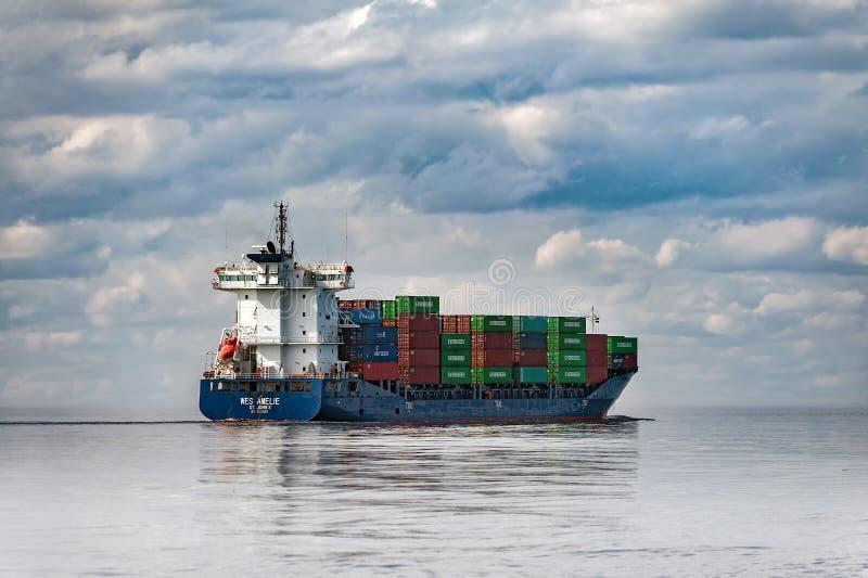 La nave del contenedor para mercancías está saliendo del puerto de Riga, Letonia imagenes de archivo