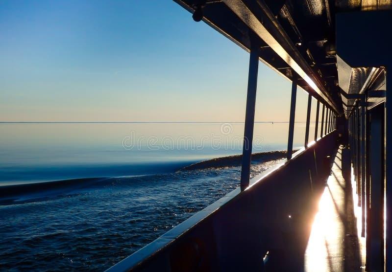 La nave del motor diseca las ondas del río en la salida del sol foto de archivo