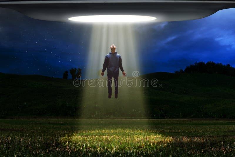 La nave espacial extranjera del UFO secuestra al ser humano imagen de archivo libre de regalías