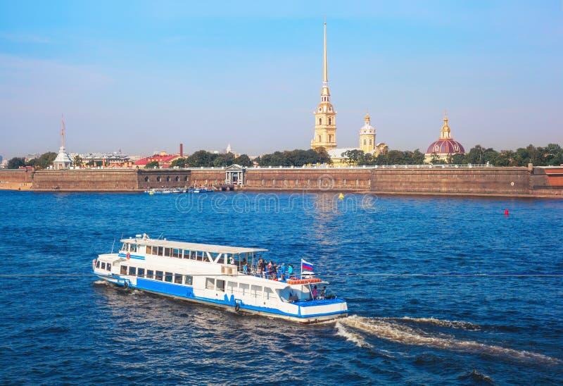 La nave navega a lo largo de Neva River cerca del Peter y de Paul Fortress foto de archivo
