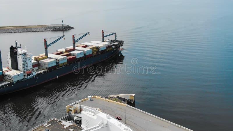 La nave porta-container caricata enorme parte porto moderno di estate immagine stock libera da diritti