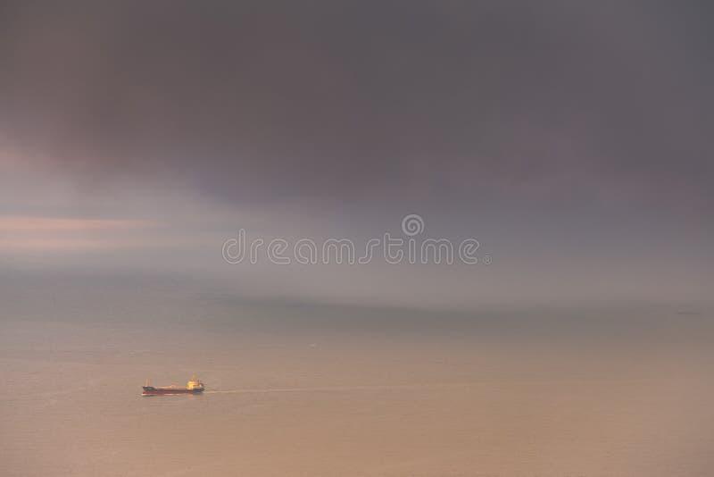 La nave porta-container supera la tempesta dietro immagini stock