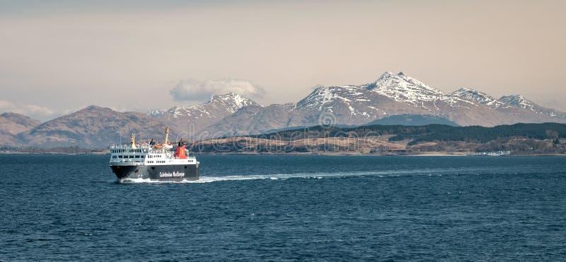 La navegación del transbordador entre Oban y la isla Mull con nieve capsuló picos de la montaña en el fondo imagen de archivo libre de regalías