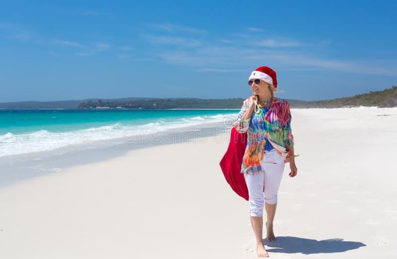 La Navidad abajo en caminar femenino del sol del verano de la playa con santa imágenes de archivo libres de regalías