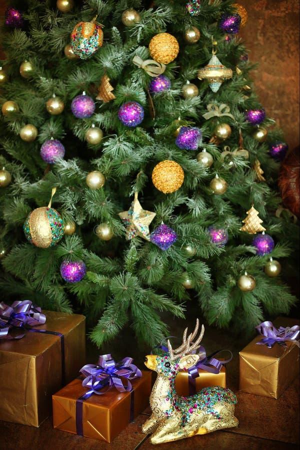 La Navidad adornó el árbol con los presentes y los ciervos imagen de archivo