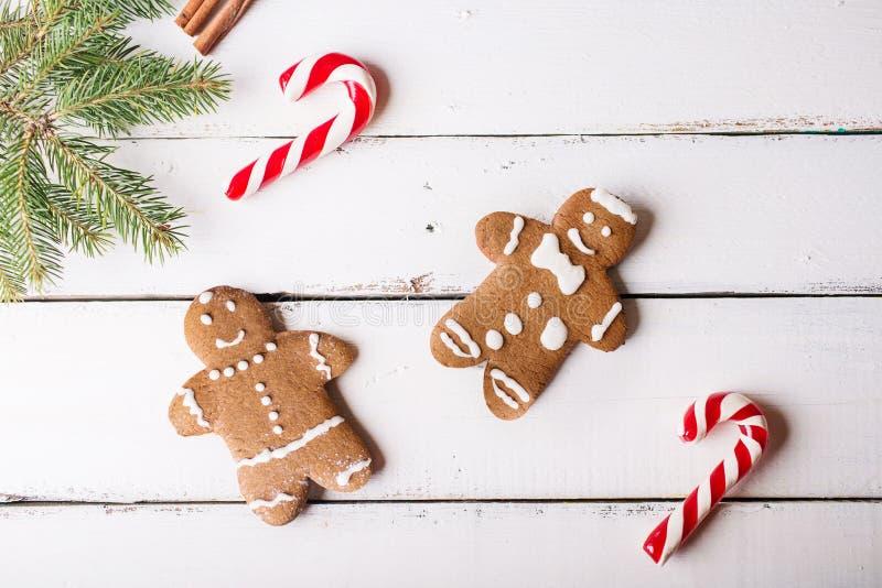 La Navidad Bastón de los hombres de pan de jengibre y de la Navidad en un fondo de madera blanco fotos de archivo