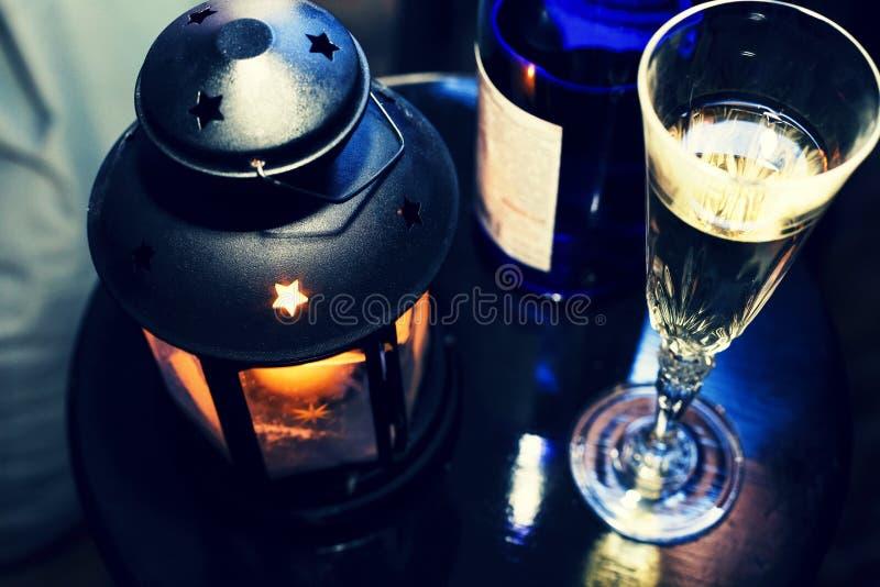 La Navidad del Año Nuevo Champán en vidrios y en una botella, una linterna de la Navidad con una vela ardiente en la tabla festiv fotos de archivo