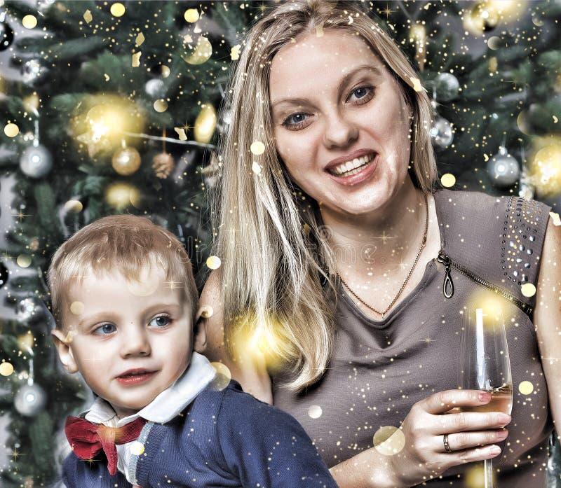 La Navidad del Año Nuevo La familia joven feliz con un pequeño hijo que sonríe feliz resuelve el Año Nuevo en casa Árbol de navid foto de archivo libre de regalías