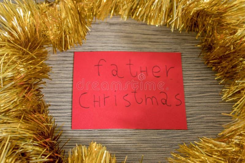 La Navidad del padre escribe en un papel rojo con las decoraciones fotos de archivo