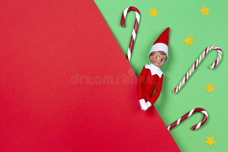 La Navidad El duende del juguete, bastones de caramelo, littlegoolden las escaleras en fondo rojo y verde Visi?n superior fotos de archivo