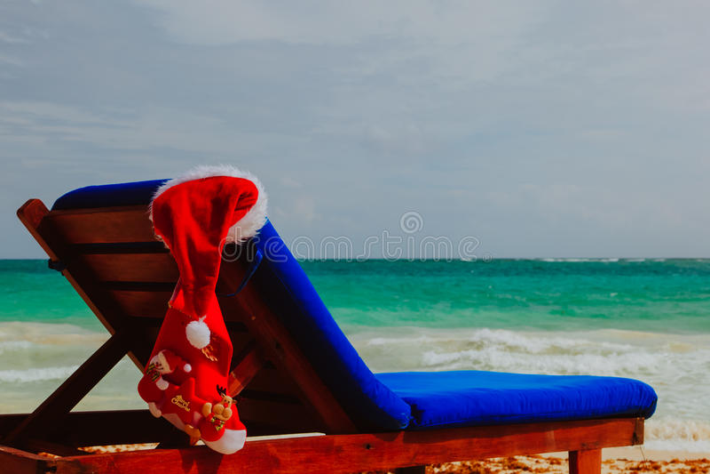 La Navidad en la playa - presida el salón con el sombrero de Papá Noel y el bolso en el mar imagenes de archivo