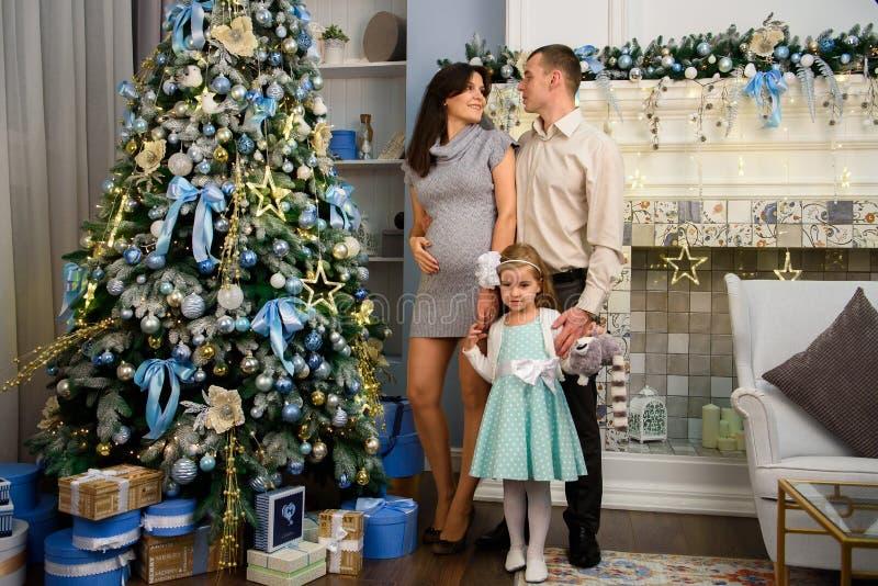 La Navidad Family Mamá y papá y su pequeña hija junto en casa imágenes de archivo libres de regalías