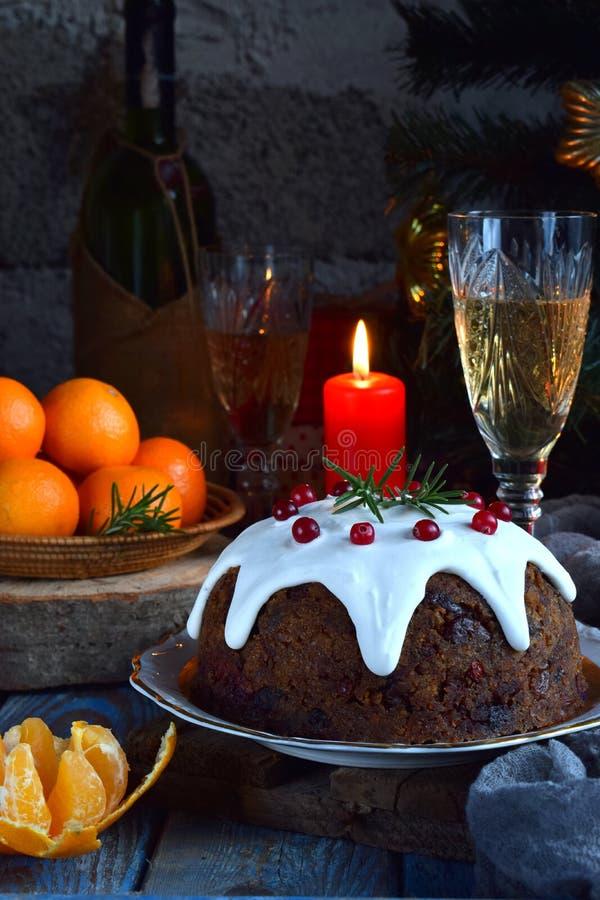 La Navidad inglesa tradicional coció el pudín al vapor con las bayas del invierno, frutas secadas, nuez en el ajuste festivo con  foto de archivo libre de regalías