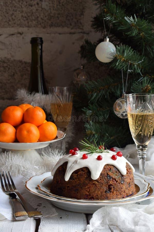 La Navidad inglesa tradicional coció el pudín al vapor con las bayas del invierno, frutas secadas, nuez en el ajuste festivo con  fotos de archivo libres de regalías