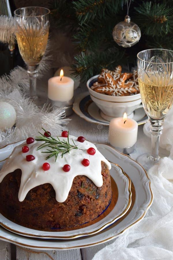 La Navidad inglesa tradicional coció el pudín al vapor con las bayas del invierno, frutas secadas, nuez en el ajuste festivo con  fotos de archivo