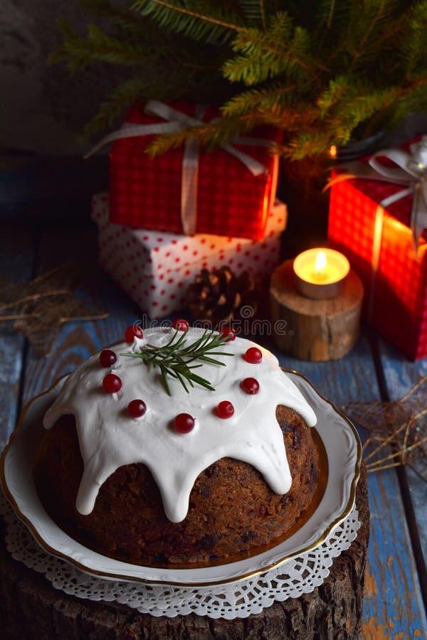 La Navidad inglesa tradicional coció el pudín al vapor con las bayas del invierno, las frutas secadas, la nuez en el ajuste festi foto de archivo libre de regalías