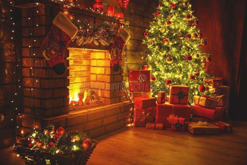 La Navidad interior árbol que brilla intensamente mágico, regalos de la chimenea en oscuridad