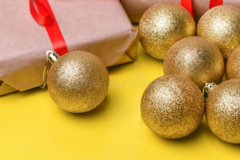 La Navidad juega bolas del color oro con lentejuelas y una caja de regalo con una envoltura de Kraft y de una mentira roja de la  imagenes de archivo