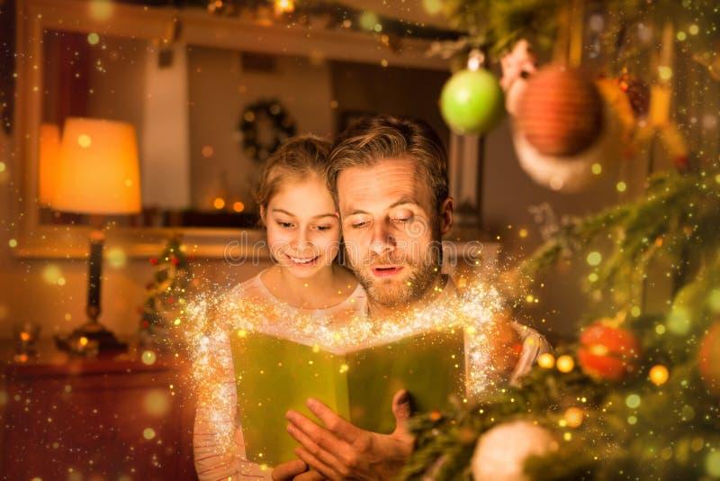 La Navidad - libro de lectura del padre y de la hija en casa fotografía de archivo libre de regalías