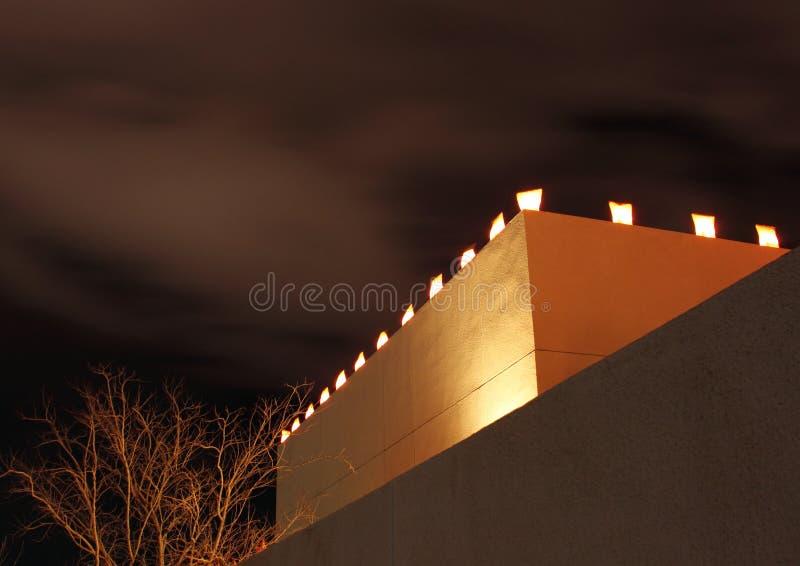 La Navidad Lumanaries en el edificio del estuco foto de archivo