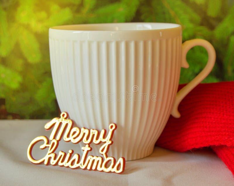 La Navidad mágica - taza blanca, copo de nieve rojo y bufanda hecha punto - tiempo acogedor de las vacaciones de invierno y etiqu imagen de archivo libre de regalías