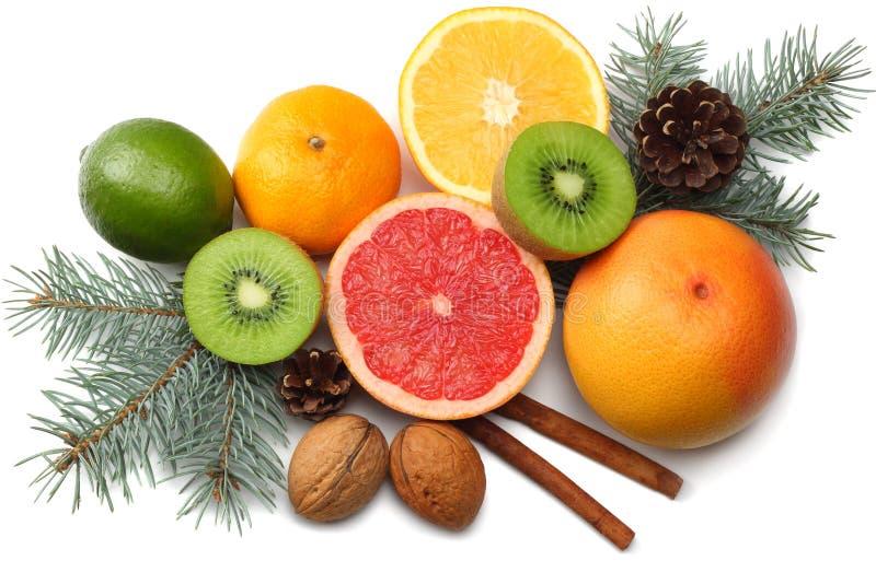 La Navidad mezcle el limón cortado, la cal verde, la naranja, el mandarín, la fruta de kiwi y el pomelo con el cono y el árbol de imagenes de archivo