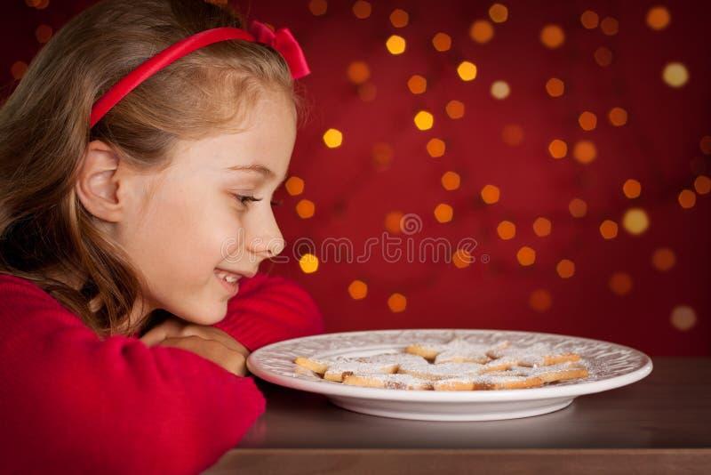La Navidad - muchacha del niño que mira la placa de las galletas en rojo oscuro con las luces fotografía de archivo libre de regalías