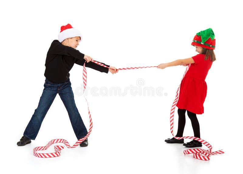 La Navidad: Muchacho y muchacha que juegan la cinta de Tug Of War With Christmas imagen de archivo