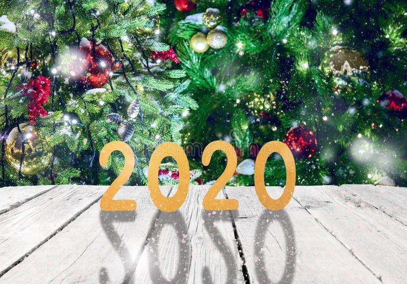 La Navidad o marco o maqueta del Año Nuevo para su proyecto 2020 fugures en de madera blanco contra los árboles de navidad de had imagen de archivo libre de regalías