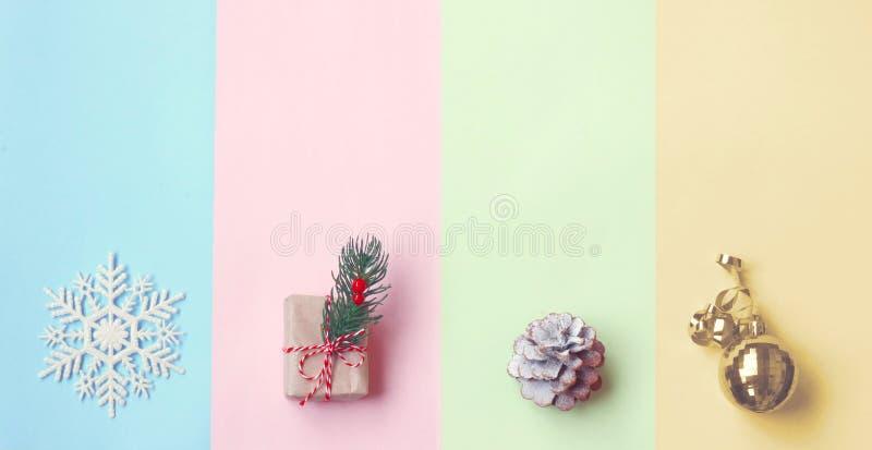 La Navidad, papel de color en colores pastel, caja de regalo, bola de oro, cono del pino fotografía de archivo