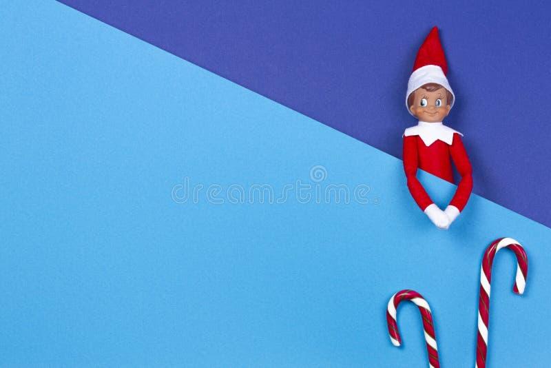 La Navidad Poco bastones del duende y de caramelo del juguete en fondo azul y azul claro multicolor Visi?n superior fotos de archivo