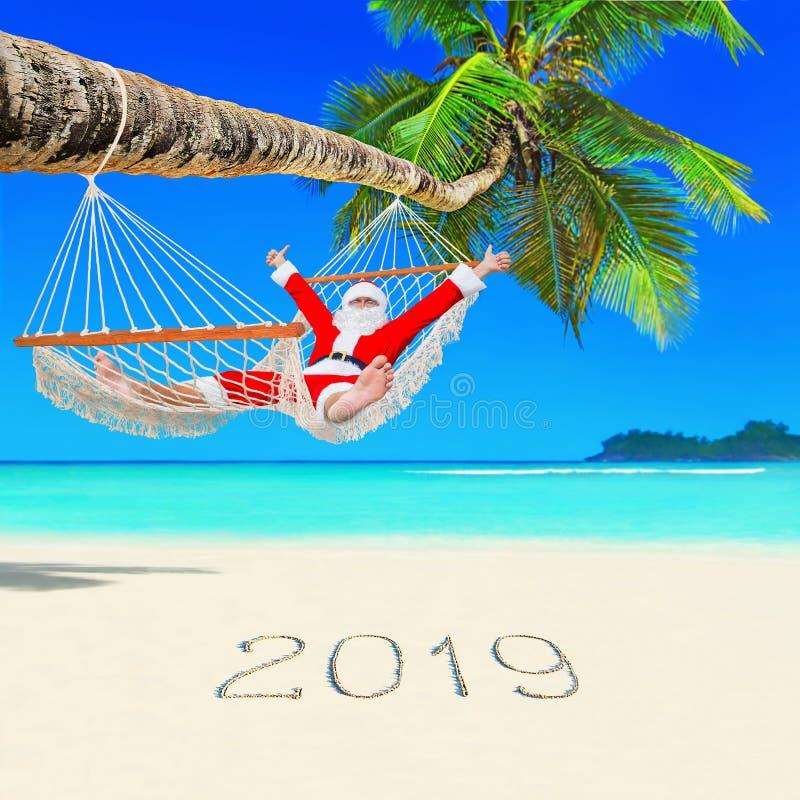 La Navidad positiva Santa Claus se relaja en hamaca en Palm Beach y el subtítulo de la Feliz Año Nuevo 2019 en la arena blanca fotografía de archivo