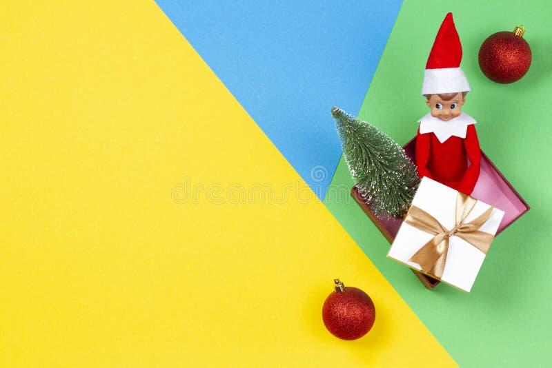 La Navidad Presente de Navidad, decoración y duende del juguete en fondo amarillo, verde y azul fotografía de archivo