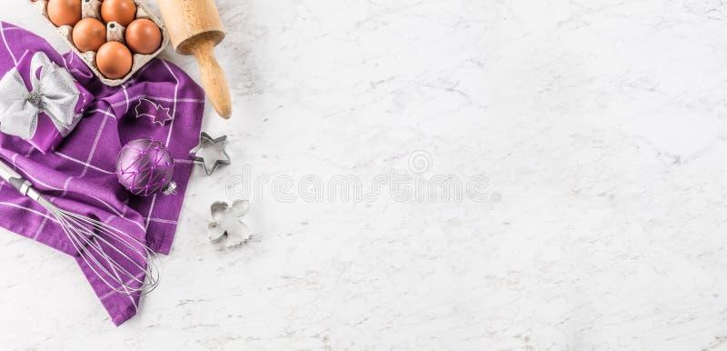 La Navidad que cuece los huevos de las decoraciones de los regalos y el utensilio púrpuras de la cocina en la tabla de mármol imagen de archivo libre de regalías