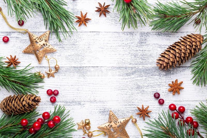 La Navidad Ramas y regalos del abeto en un fondo de madera ligero Arándanos, especias, bayas del acebo imagen de archivo